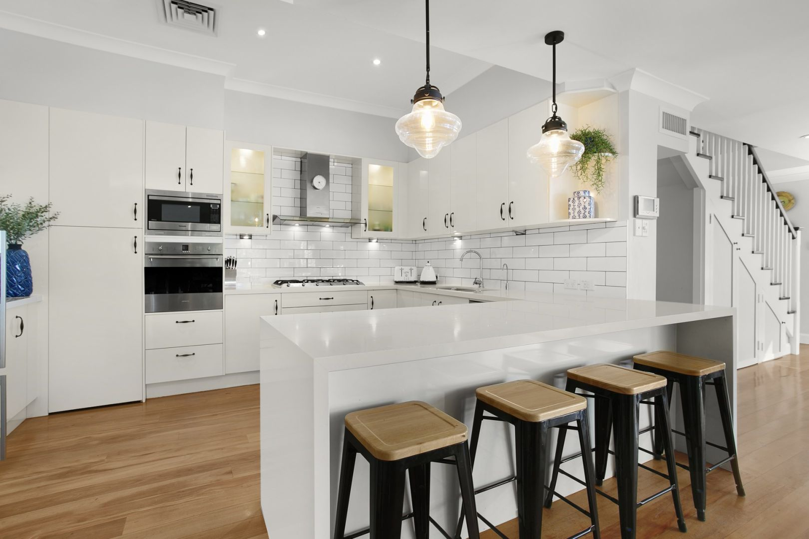 White Kitchen Cabinet with Wooden Floor and Chair